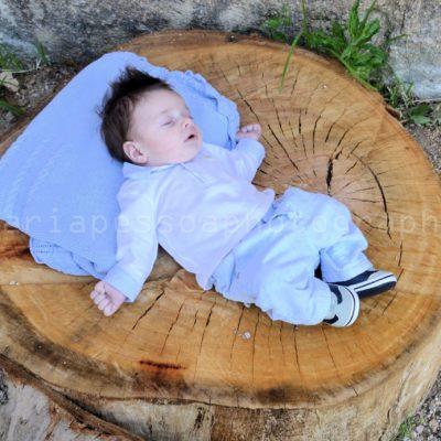 Fotografia profissional de rosto de menino de perfil, deitado sobre um tronco