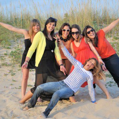 fotografia profissional de raparigas a acenar na areia da praia