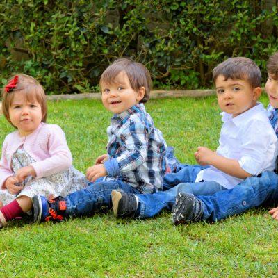 fotografia de quatro crianças sentadas na relva