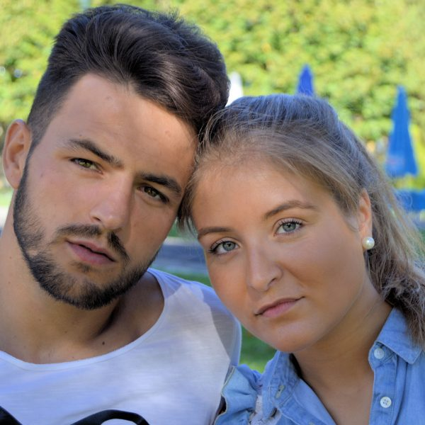 Retrato profissional de casal jovem encostados. Fotografia profissional de exterior.