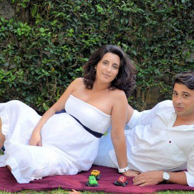 Fotografia profissional de grávida com o marido sentados na relva