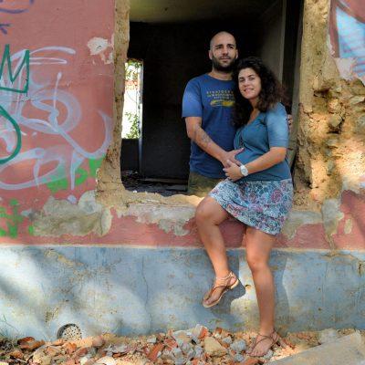 Fotografia profissional de grávida com o marido sentados na janela de uma casa em ruínas