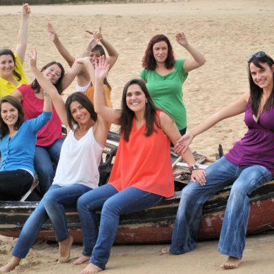fotografia profissional de raparigas sentadas num barco na praia