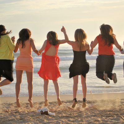 fotografia profissional de raparigas a saltar de costas na praia