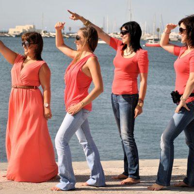 fotografia profissional de raparigas a apontar para longe na praia