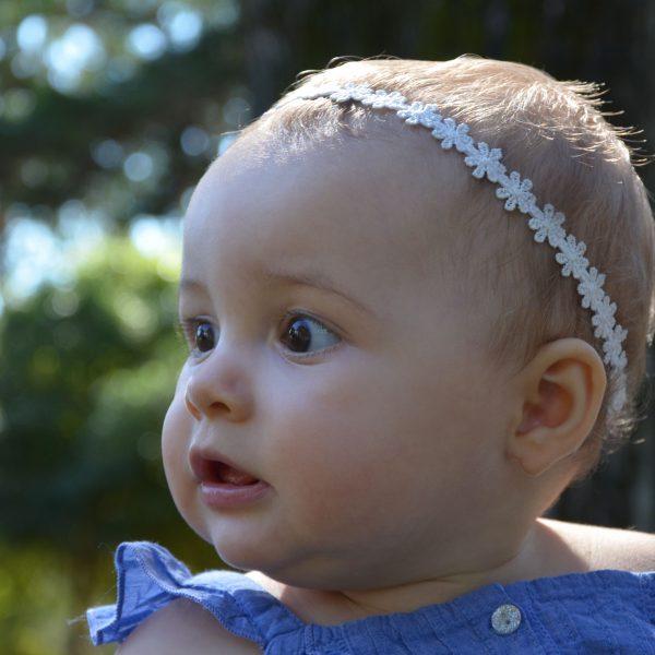 Fotografia profissional de rosto de bebé com coroa de flores
