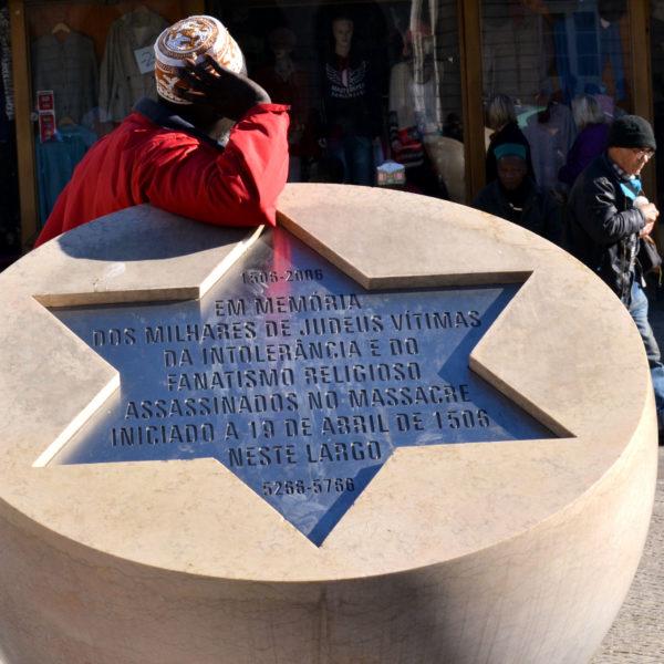 Fotografia profissional de homem africano encostado a monumento em memória dos judeus