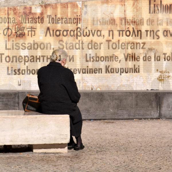 Fotografia profissional de idosa sentada em frente ao mural da tolerância em Lisboa.