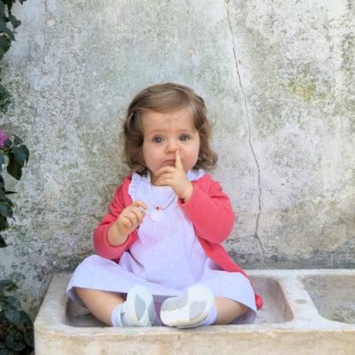 Fotografia profissional de menina sentada numa fonte.
