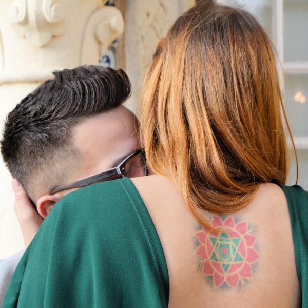 Retrato profissional de casal jovem de costas, de modo a verem-se as tatuagens. Fotografia profissional de exterior.