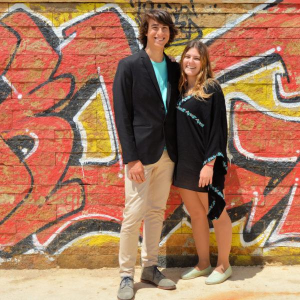 fotografia de casal jovem encostados a parede com graffiti. Fotografia profissional de exterior.