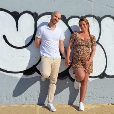 Casal na praia encostados a parede com graffiti. Fotografia de grávida.
