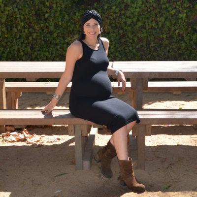 Fotografia de mulher grávida sentada num jardim com turbante no cabelo
