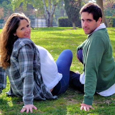 Casal no jardim, a senhora está grávida e ambos olham para trás.