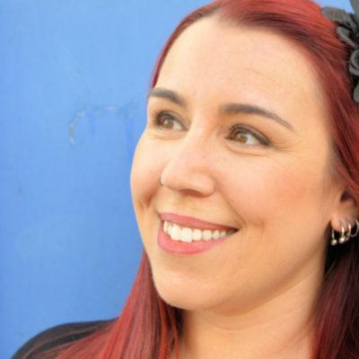 Retrato profissional feminino de mulher ruiva sorridente.